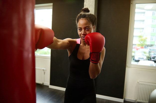 African sports woman boxer wearing red boxing gloves hitting a punching bag at boxing gym. martial combat art concept. hard workout, active and healthy lifestyles concept, sport, energy, vitality