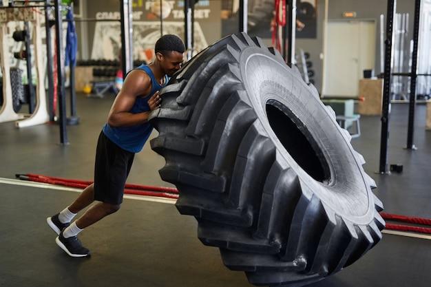 Африканский спортсмен переворачивает шину в тренажерном зале