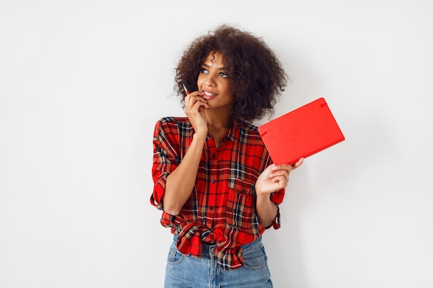 African student female with book posing   indoor over white  wall. wearing red checkered shirt. blue jeans.