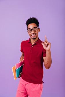 Studente africano in abbigliamento rosso in posa con un sorriso interessato. uomo nero di buon umore con gli occhiali che tiene libri ed esprime felicità.