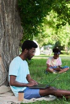 草の上に座って、公園でラップトップに取り組んでいるアフリカの学生