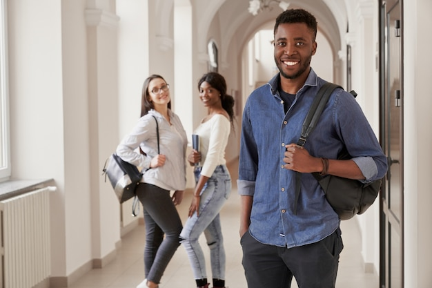 African student wearing blue shirt holding notes, going to lecture and smiling. happy male studying at international university. two pretty girls with backpacks on background.