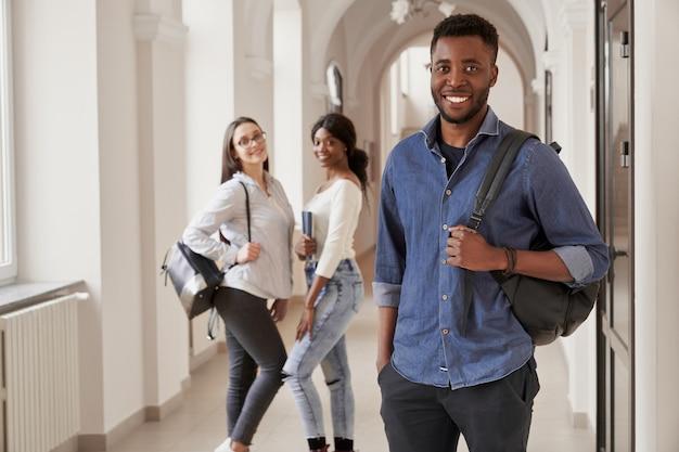 노트를 들고, 강의 하 고 웃 고 파란색 셔츠를 입고 아프리카 학생. 국제 대학에서 공부하는 행복 한 남자. 배경에 배낭과 두 예쁜 여자입니다.