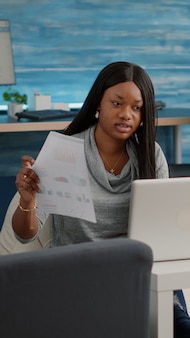 African student working from home at marketing strategy typing financial graphs