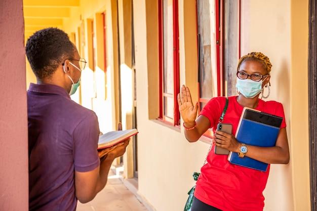 物理的な距離を観察している学校のアフリカの学生