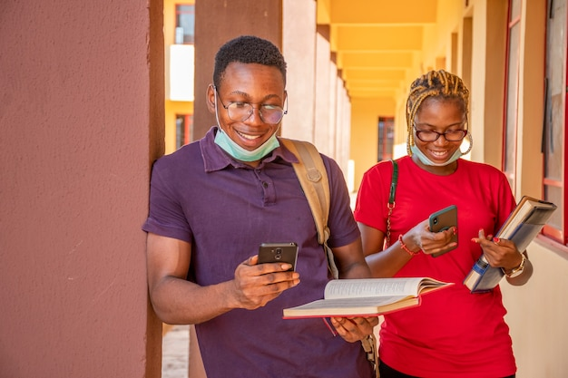 African students wearing face masks using their mobile phones