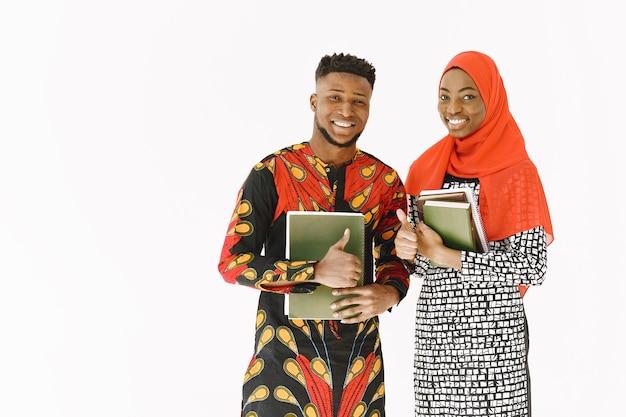 아프리카 학생들. 전통적인 나이지리아 옷을 입은 젊은 사람들. 책을 들고. 연구 개념.