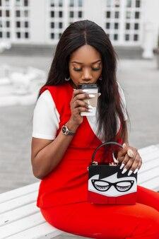 ファッショナブルな赤いスーツを着たアフリカのスタイリッシュな若い女性が路上でコーヒーを飲みます。ヴィンテージのハンドバッグと若者の流行の服を着たかわいい黒人の女の子は、街の建物の近くのベンチに座っています。女性のためのファッションウェア。