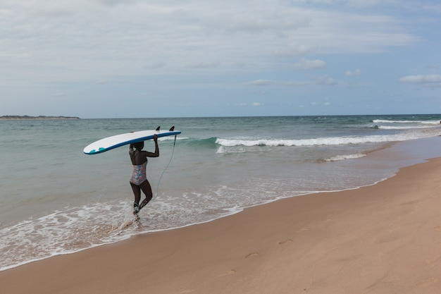 Африканский серфер девушка идет с доской для серфинга к океану