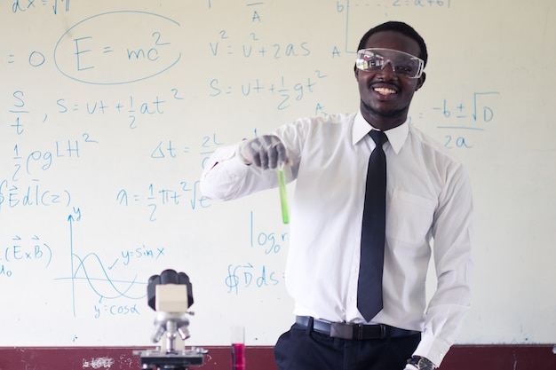African teachers wear glasses while experimenting with science class.