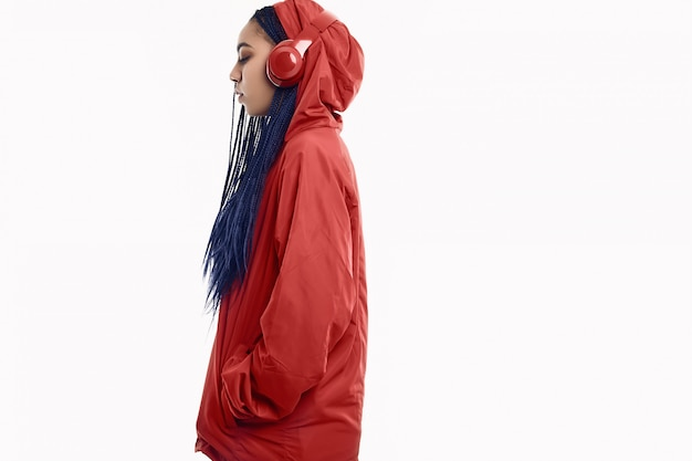 African teenage girl with dreadlocks in red windbreaker listening music