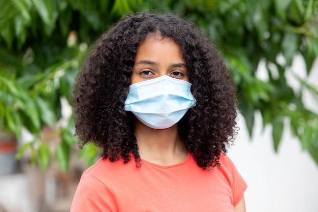 ウイルスから身を守るためにマスクをかぶったアフリカのティーンエイジャー