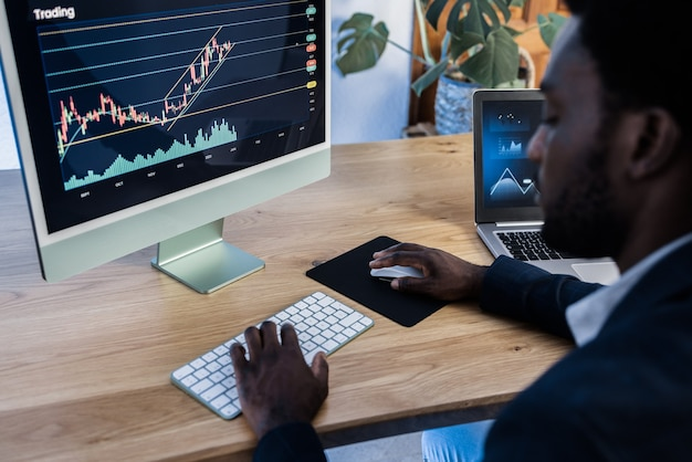 African trader studying stock market at home - focus on computer screen