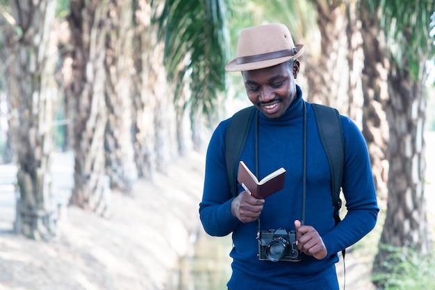 아프리카 여행자 남자 카메라를 들고 미소와 행복으로 여권을 찾고