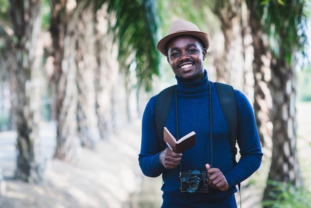 미소와 행복으로 카메라와 여권을 들고 아프리카 여행자 남자