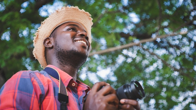 African traveler man holding a camera in the green nature bokeh background