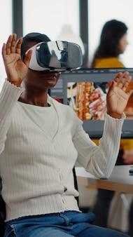 Африканский видеоредактор испытывает очки виртуальной реальности, жестикулируя, редактируя видео, монтаж фильма, работая с ...