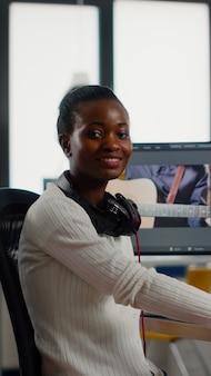 후반 제작 소프트웨어 작업에서 카메라 미소 편집 비디오 프로젝트를 보고 있는 아프리카 비디오 편집자