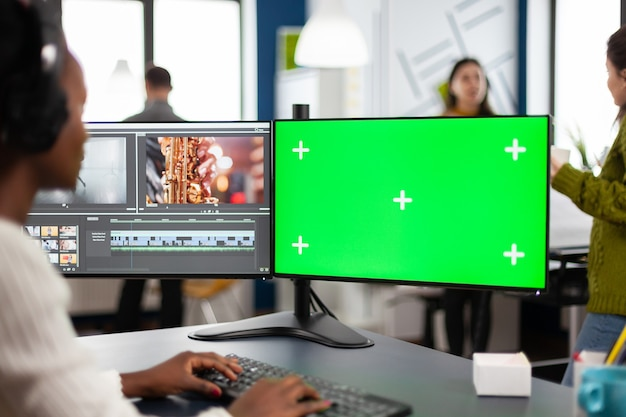 African video editor with headset editing footage using pc with greenscreen, chroma key isolated display sitting in creative agency