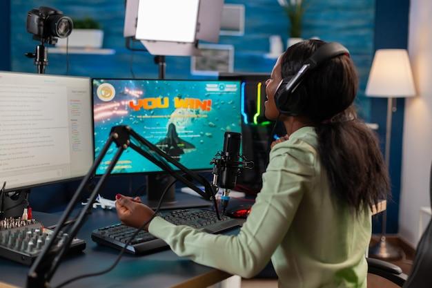 아프리카 비디오 게임 e 스포츠 선수가 챔피언십 우승 후 비명을 지르는 동안 마이크에 대한 이야기를 스트리밍합니다. 네온으로 집에서 비디오 게임 토너먼트 중 온라인 스트리밍 사이버 공연