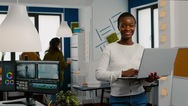 Африканский видеооператор поднимает голову, улыбаясь в камеру после набора текста на ноутбуке