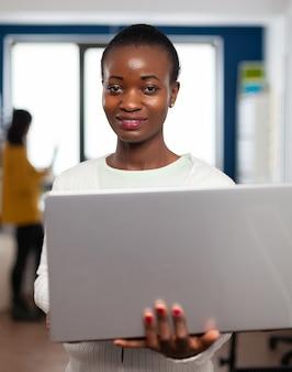 クリエイティブエージェンシーオフィスに立っているラップトップで保持しているカメラに微笑んでアフリカのビデオグラファー