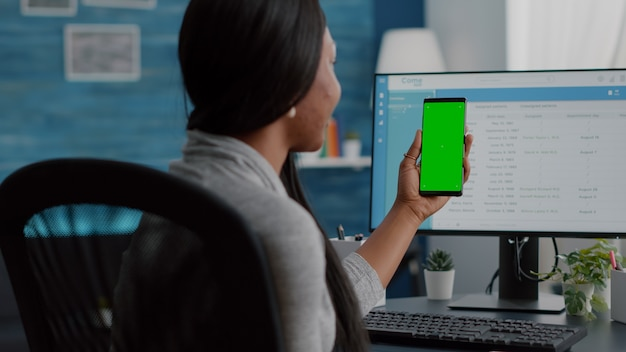 African woman analyzing social media video using mock up green screen chroma key phone with isolated display working remote from home sitting at desk in living room