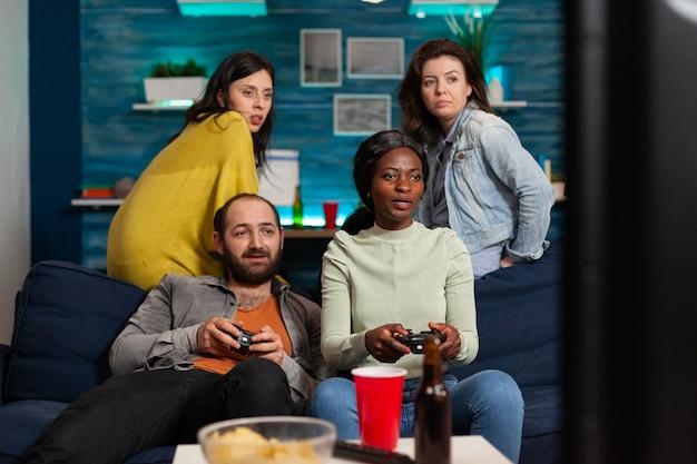 Африканская женщина и многоэтнические друзья играют в видеоигры поздно вечером, сидя на диване, используя беспроводной контроллер, общаются. группа людей, весело проводящих время.