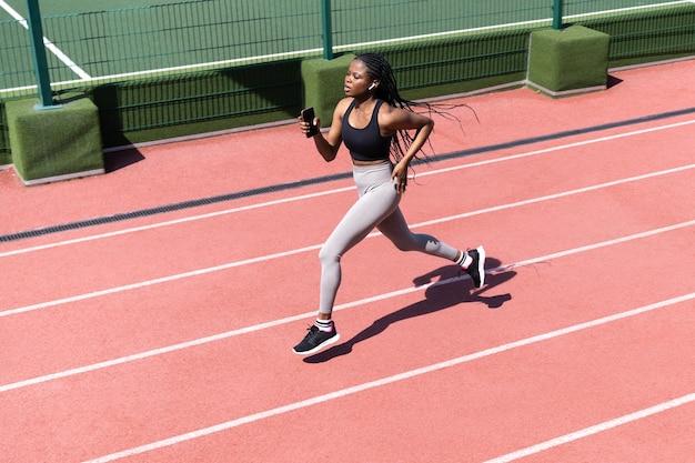 African woman athlete running on racetrack sportive black female training jog on stadium sprinting