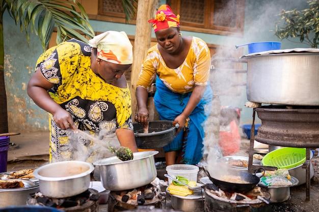 通りで伝統的な料理を調理するアフリカの女性