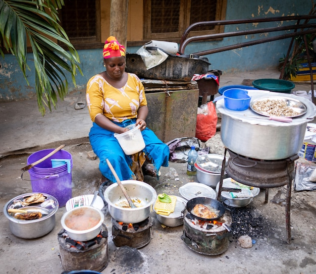 African woman cooking traditional food at street