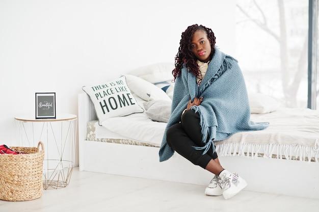 アフリカの女性が自宅で空白の格子縞でカバー
