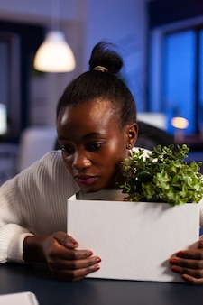 African woman depressed at night after bing let go from work because of downsizing