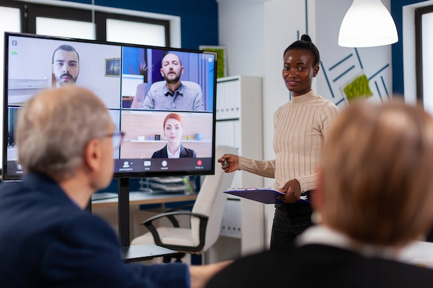 African woman discussing with remote managers on video call presenting new partners on webcam. business people talking to webcam, do online conference participate internet brainstorming, distance office