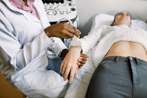 African woman doctor hand with ultrasound scanner doing the examination on the hand of young patient
