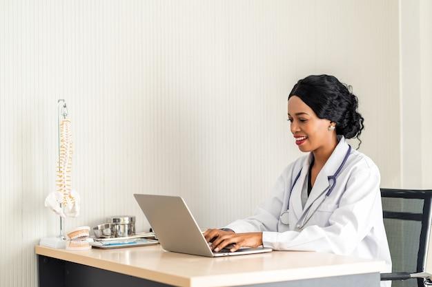 통증 환자를 위해 온라인으로 그녀의 헤드셋 마이크에 전화를 복용 헤드셋에서 아프리카 여자 의사