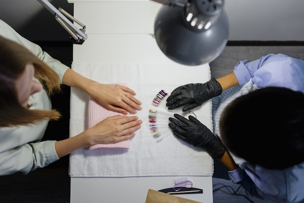 An african woman does a manicure for a european woman the process of manicure in a studio or beauty