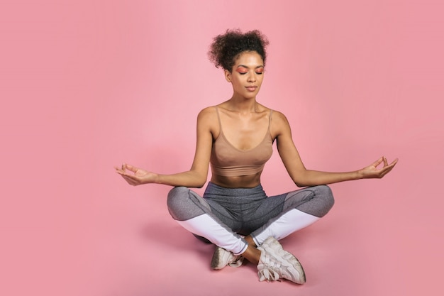 スタジオでヨガをやっているアフリカの女性。ピンクの背景。