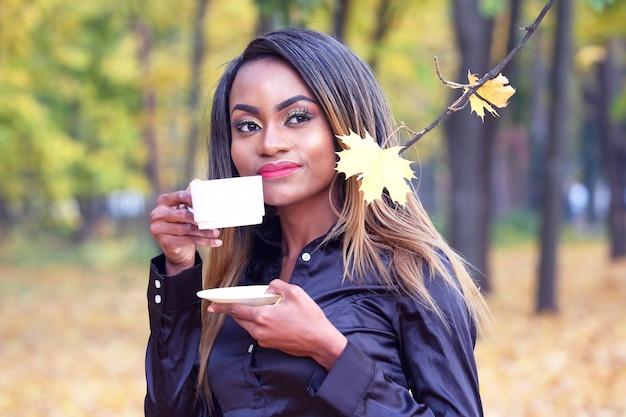 Африканская женщина пьет кофе из белой чашки на фоне осенних листьев в парке