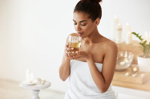 Африканская женщина, пить зеленый чай, отдыхая в спа салоне.