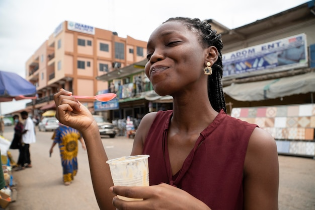 Donna africana che mangia una bevanda fredda