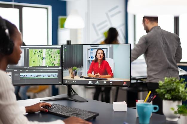 화상 통화 편집 클라이언트 작업에 대해 파트너와 온라인 회의 중에 헤드셋을 사용하는 아프리카 여성 편집자, 사무실의 pc에서 포스트 프로덕션 소프트웨어를 사용하여 상업 영화에 대한 피드백 받기