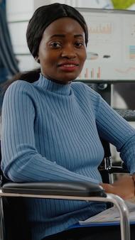 휠체어에 앉아 웃는 카메라를 보고 아프리카 여성 직원