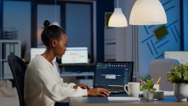 신생 비즈니스 사무실의 책상에 장비를 놓고 현대적인 cad 프로그램에서 일하는 아프리카 여성 엔지니어. 장치 디스플레이에 cad 소프트웨어를 보여주는 랩톱에서 프로토타입 아이디어를 연구하는 산업 직원