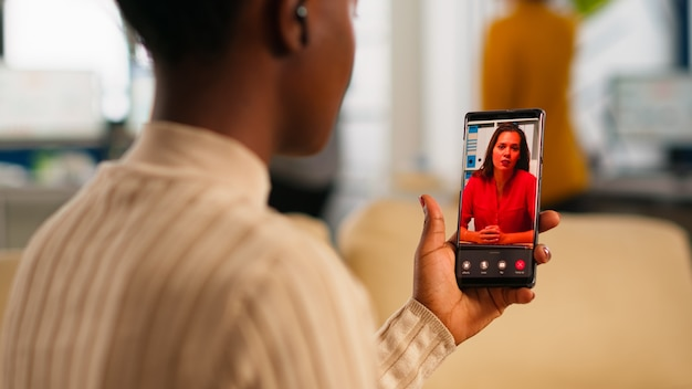 African woman explaining financial reports to remote manager on video call holding smartphone using headphones sitting on couch in business modern office. diverse coworkers planning financial project