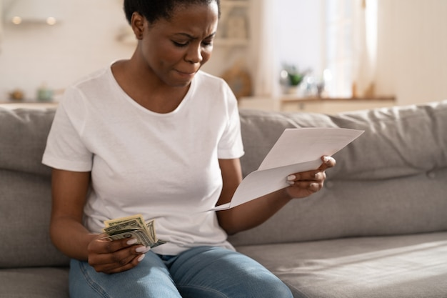 African woman frustrated about lack of finances, feeling anxiety about overdue mortgage payment.