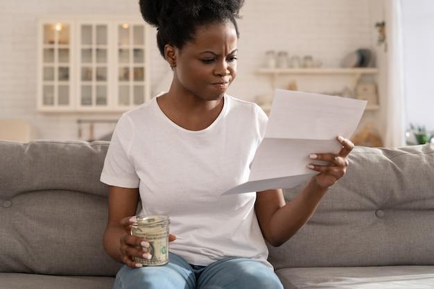 Африканская женщина расстроена нехваткой финансов, испытывая беспокойство по поводу просрочки платежа по ипотеке.
