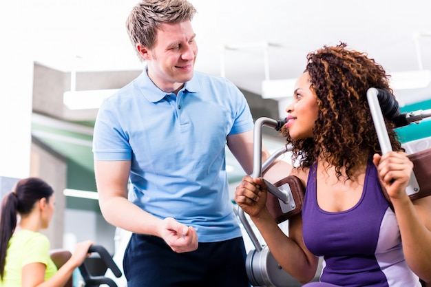 African woman in gym exercising with personal trainer