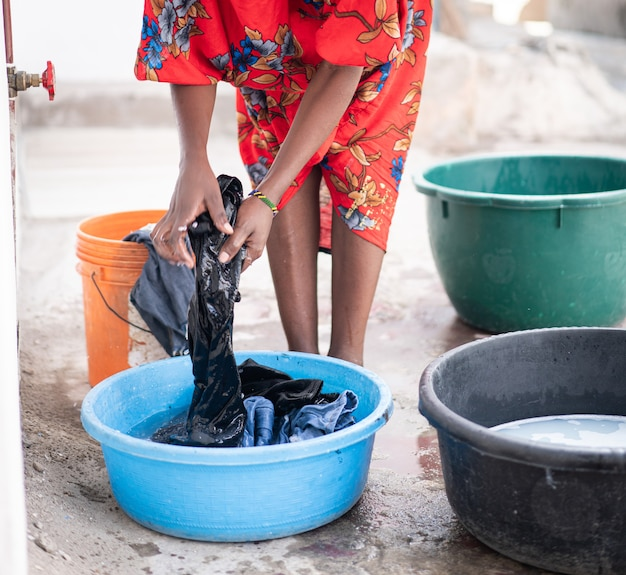 African woman hand washing laundry outdoors