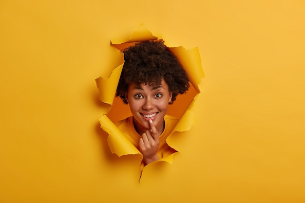 African woman has broad smile, expresses optimism, shows white teeth, holds hand on chin, shares positive memories, poses in ripped hole of yellow background